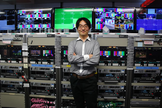 Kazunori standing in front of a wall of broadcast equipment and screens.
